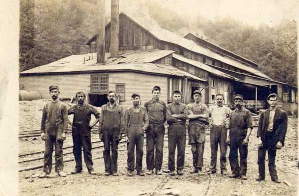 Group of men in front of factory